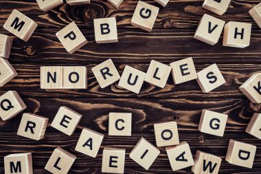 top view of no rules lettering made of wooden cubes on brown wooden tabletop