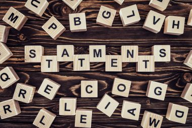 top view of of word statements made of wooden blocks on wooden surface