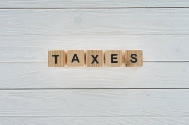 top view of wooden blocks arranged in taxes word on white wooden tabletop
