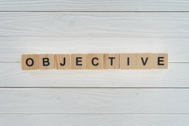 top view of objective word made of blocks on white wooden surface