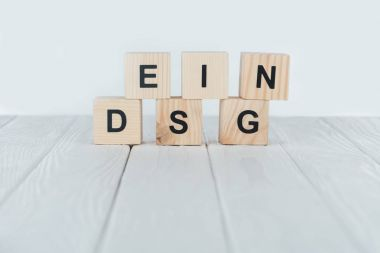 close up view of design word made of wooden cubes on white wooden tabletop