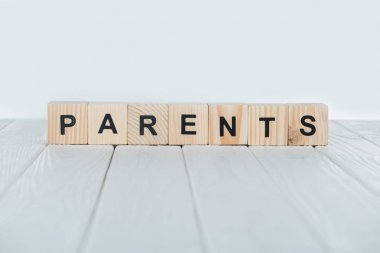 close up view of parents word made of wooden cubes on white wooden tabletop