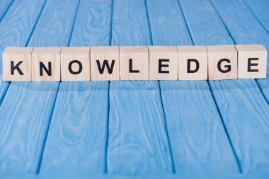 close up view of knowledge word made of wooden blocks on blue tabletop