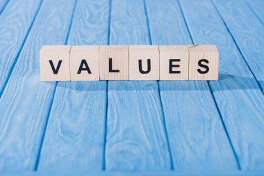 close up view of values word made of wooden blocks on blue tabletop