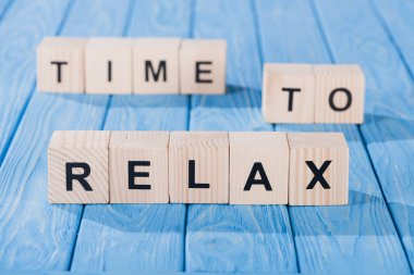 close up view of arranged wooden blocks into time to relax phrase on blue wooden surface