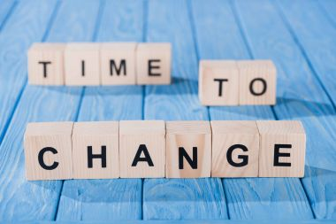 close up view of arranged wooden blocks into time to change phrase on blue wooden surface