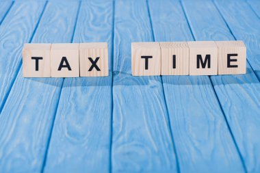 close up view of arranged wooden blocks into tax time phrase on blue wooden surface