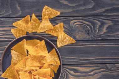 top view of crispy unhealthy nachos in bowl on wooden table