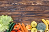 Fotografie top view of fresh healthy fruits and vegetables on wooden table