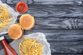 Photo top view of hamburgers with french fries and ketchup on wooden table
