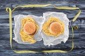 Draufsicht der zwei Hamburger mit Pommes frites und ein Maßband auf Holztisch