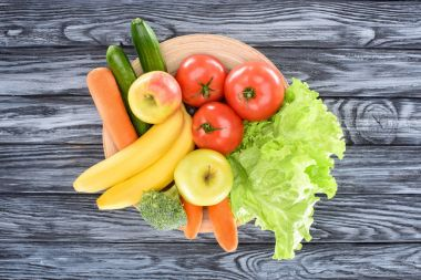 top view of fresh ripe fruits and vegetables on plate on wooden table