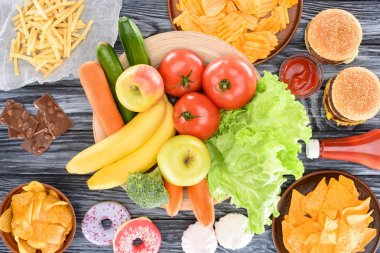 top view of assorted junk food and fresh fruits with vegetables on wooden table