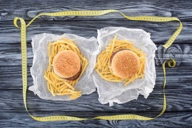 top view of two hamburgers with french fries and measuring tape on wooden table