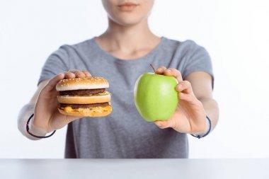 close-up view of woman holding fresh ripe apple and hamburger