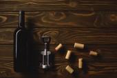 Fotografie horní pohled na luxusní červená vína s zátky a vývrtka na dřevěný stůl