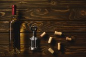 horní pohled na láhev bílého vína s zátky a vývrtka na dřevěný stůl