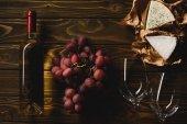 pohled shora láhev bílého vína s brýlemi, hrozny a sýr na dřevěný stůl
