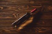 Fotografie pohled shora na láhev bílého vína na dřevěný stůl