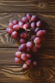 top view of branch of ripe red grapes on wooden table