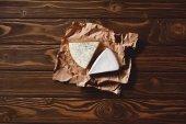 pohled shora na plátky sýra na zmačkaný papír na dřevěný stůl