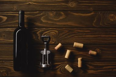 top view of bottle of luxury red wine with corks and corkscrew on wooden table