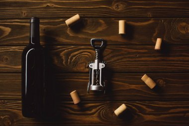 top view of bottle of luxury red wine with corkscrew surrounded with corks on wooden table