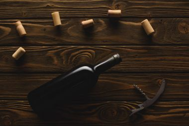 top view of bottle of red wine with corks and corkscrew on wooden table