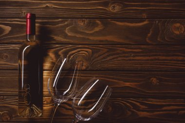 top view of bottle of white wine with empty glasses on wooden table