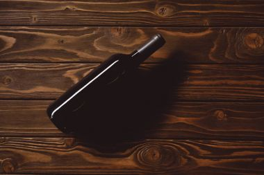 top view of bottle of red wine on wooden table