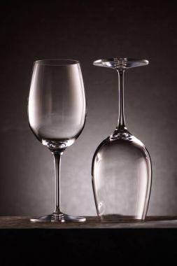 two reversed empty wineglasses on black