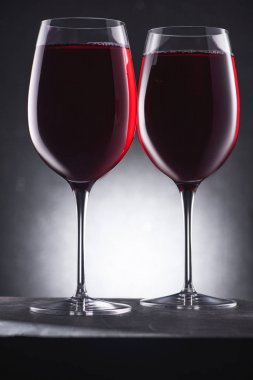 close-up shot of glasses full of delicious red wine on black