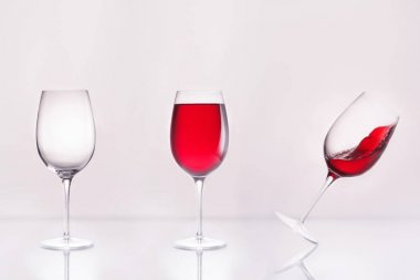 empty wineglass with full and inclined in row on reflective surface and on white