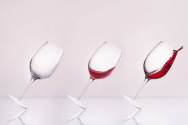 row of inclined wineglasses empty and with splashing wine on reflective surface and on white