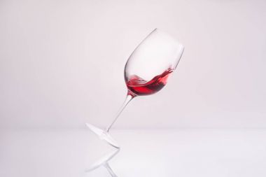 inclined glass with splashing red wine on reflective surface and on white