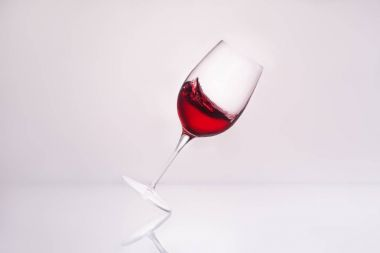 inclined wineglass with splashing red wine on reflective surface and on white