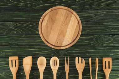 top view of round cutting board and kitchen utensils placed in row on wooden table