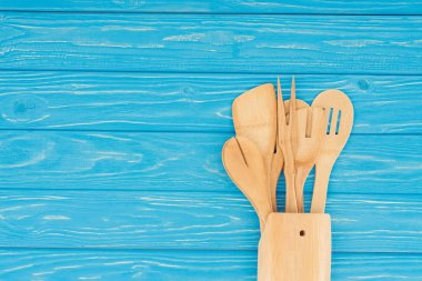 top view of different wooden kitchen utensils on blue table