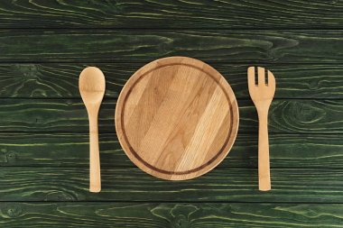 top view of round cutting board between fork and spoon on wooden table