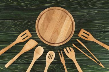 top view of round cutting board and wooden kitchen utensils on table