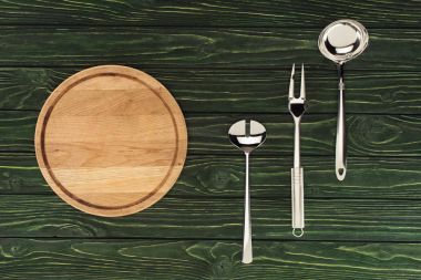top view of round wooden cutting board and metallic kitchen utensils on table