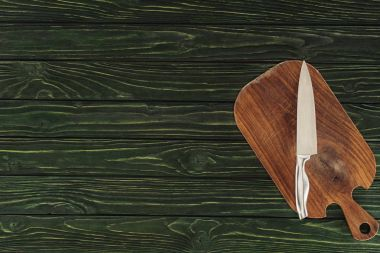top view of knife on wooden cutting board on table