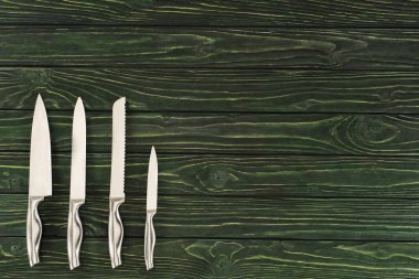 top view of different types of knifes on wooden table