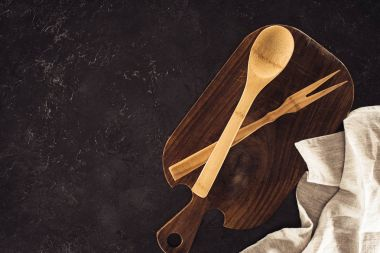 top view of spoon, fork for meat on wooden cutting board and sackcloth on marble table