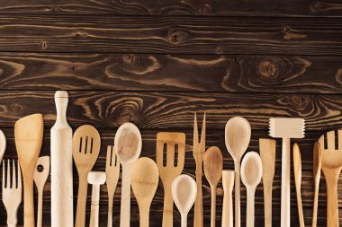 top view of kitchen utensils placed in row on wooden table