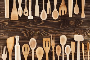 top view of kitchen utensils placed in rows on wooden table