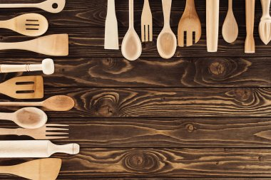 top view of kitchen utensils placed in two rows on wooden table