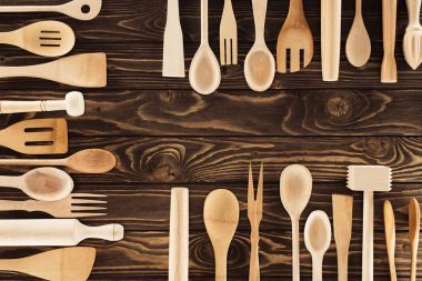 elevated view of kitchen utensils placed in three rows on wooden table