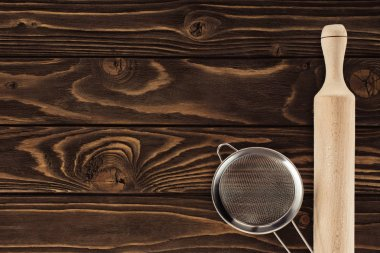 top view of sieve and wooden rolling pin on table