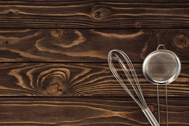top view of whisk and sieve on wooden table
